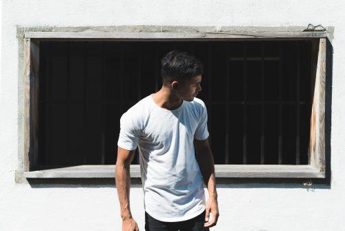 Homme avec un jean et un t-shirt blanc devant un mur