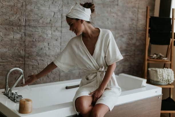 Femme en peignoir blanc qui fait couleur son bain